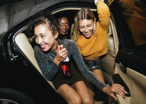 An image of of some women on a night out getting out of a taxi
